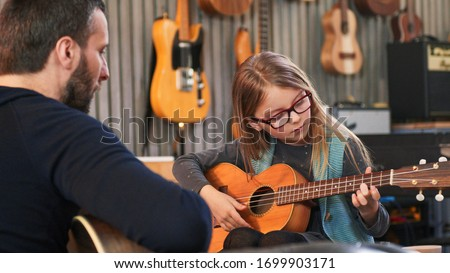 Dad teaching guitar and ukulele to his daughter.Little girl learning guitar at home.Close up.Ukulele class at home. Child learning guitar from her father ストックフォト ©