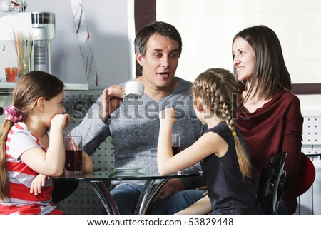Dad tells story to family sitting in cafe at table