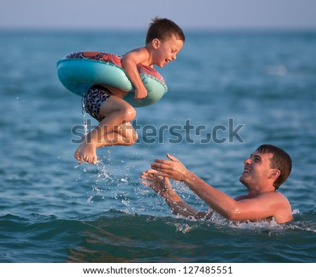 Dad throws up his son in an inflatable circle in the sea