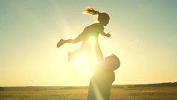 Dad tosses a happy child up into the sky at sunset. Daddy s daughter flies in his arms soaring in the air playing the game plane in the glare of the sun. The little kid rejoices with his father at