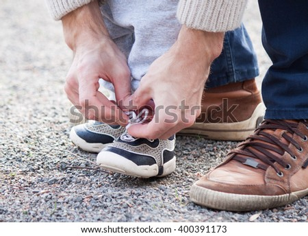 Dad tying the laces on a child sneakers #400391173
