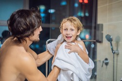 Dad wipes his son with a towel after a shower in the evening before going to sleep on the background of a window with a panoramic view of the city