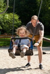 Dad with child on the playground, vertical