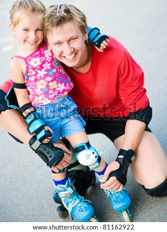Dad with his little daughter on the skates
