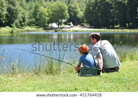 Dad with little boy fishing by mountain lake