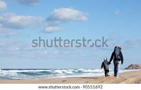 Dad with son walking on a winter beach