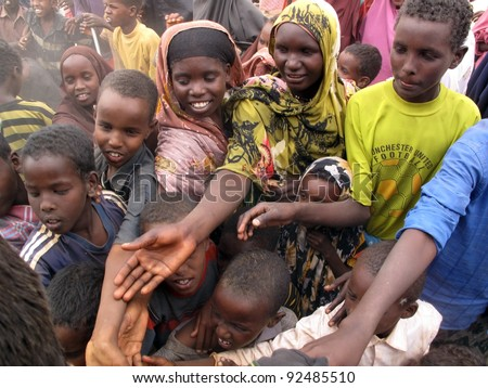 DADAAB, SOMALIA-AUGUST 15: unidentified children stretch out their hands at the Dadaab refugee camp where thousands of Somalian wait for help because of hunger on August 15, 2011, in Dadaab,Somalia.