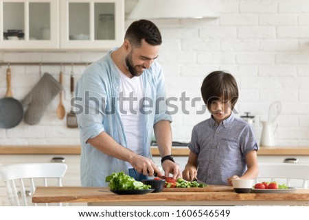Daddy and little son cooking veggie salad together in kitchen preparing surprise for mom. Accustom child to work, teaching process, sharing skills, preparation of healthy fresh domestic food concept