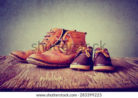 Daddy\'s boots and baby\'s shoes, fathers day concept.