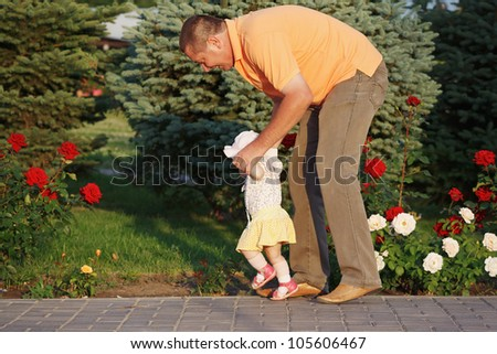 Daddy teaches her beautiful little daughter to walk on the background of rose bushes