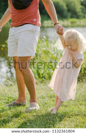 Daddy with a daughter on a picnic. A beautiful, pretty photo with a curly little blonde girl