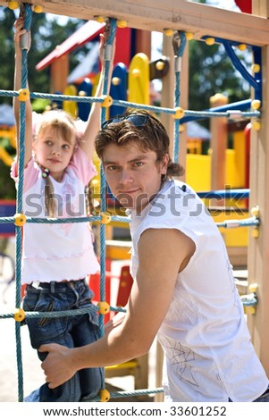 Daddy with  daughter in park on  playground. Happy family.
