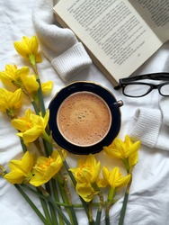 Daffodils, coffee cup, book and reading glasses sitting on the bed. Relaxing at home, hygge and staying at home concept. Spring background.