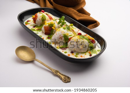 Dahi vada or bhalla is a type of chaat originating from the Indian and popular throughout South Asia. It is prepared by soaking vadas in thick dahi or curd. selective focus Сток-фото ©