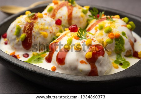 Dahi vada or bhalla is a type of chaat originating from the Indian and popular throughout South Asia. It is prepared by soaking vadas in thick dahi or curd. selective focus Zdjęcia stock ©