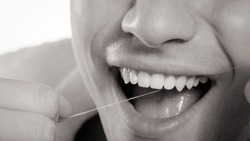 Daily health care. Young man cleaning flossing his white teeth with dental floss, black & white photo