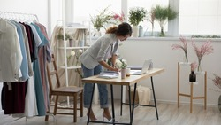 Daily routine. Concentrated young self employed woman dressmaker stand by desk at workspace focused on paperwork. Female decorator floral designer planning checking order information at cozy showroom