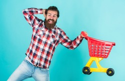 Daily task. brutal mature hipster go shopping. Its time to fill the cart. man go shopping. funny man with small shopping cart. weekend on buying products. rejoices successful purchases.