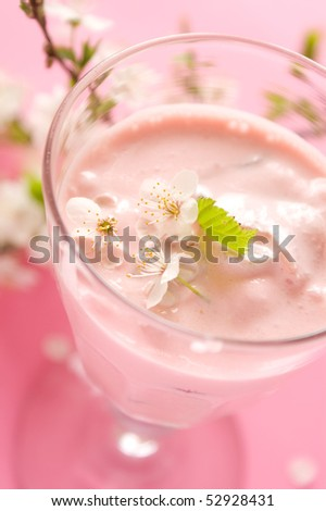 Dairy cocktail in the high glass, decorated with flowers. On a pink background