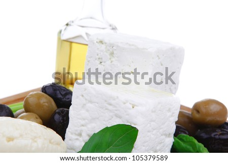dairy food : feta white cheese cubes and round served on wooden cut plate with green leaves and olive oil isolated over white background