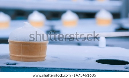 Dairy industry, manufacturing and automated technology equipment concept - conveyor belt with icecream cones at modern food processing factory - icecream automatic production line