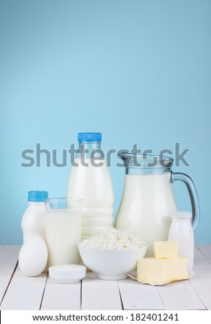 Dairy products assortment on wooden table, blue background, copy space