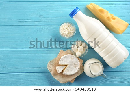 Dairy products on wooden background, top view