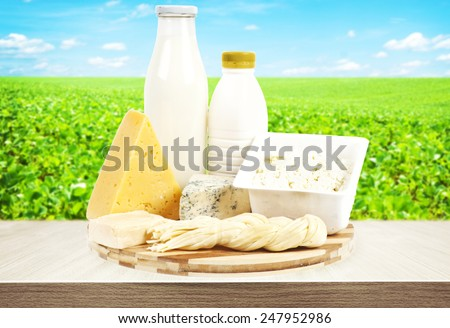 Dairy products on wooden table and field with green grass on background