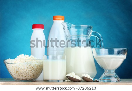 Dairy products on wooden table on blue background - stock photo