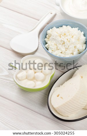 Dairy products on wooden table. Sour cream, milk and cheese. Top view