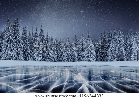 Dairy Star Trek above the winter woods. Cracks on the surface of the blue ice near hills of pines. Frozen lake in mountains. Carpathian Ukraine Europe.