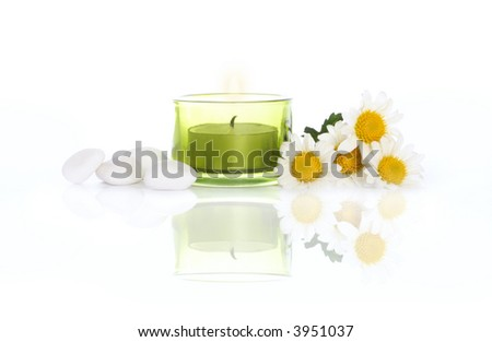 Daisies, white river stones and candle on white background