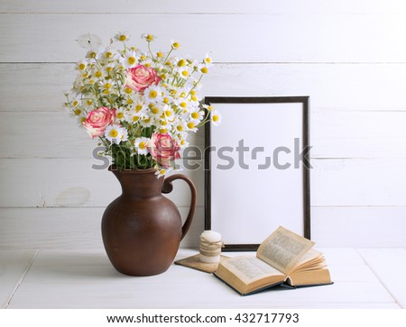 Daisy bouquet with roses in clay jug with open book and motivational frame  for your text or picture on background of white wooden planks in scandinavian style. Home interior.