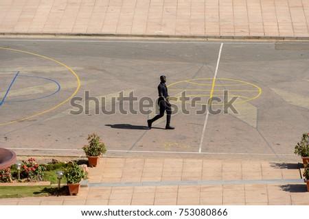 DAKAR, SENEGAL - APR 23, 2017: Unidentified Senegalese policeman walks along basketball field in Dakar, the capital of Senegal #753080866