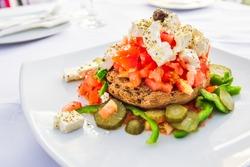 Dakos, Cretan salad with fresh vegetables, feta cheese and olives, Greece traditional cuisine.