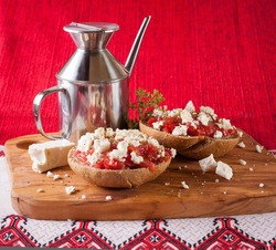 Dakos, Crete meze with barley rusk paximadia with tomato, feta or myzithra cheese and oregano and olive oil with metal oilcan on the olive wood cutting board and white ornament cloth horizontal