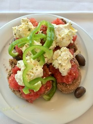 Dakos traditional Greek appetizer on a white plate with olive oil, dry rye bread, olives, feta cheese and tomatoes. Healthy eating concept. Mediterranean lifestyle.