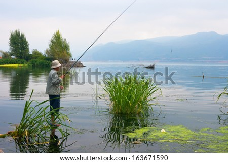 DALI, CHINA, CHINA - SEP 24: Man fishing in Erhai Lake  on Sep 24, 2011 in Dali,  Erhai Lake is second largest freshwater lake in Yunnan,Area of ??256.5 square kilometers