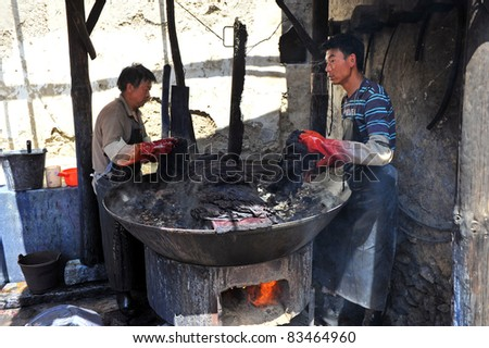 DALI, CHINA - JULY 22: Unidentified men of Chinese Bai ethnic minority making batik (textile dyeing) on July 22, 2011 in Dali, China. These people depend on batik as a way to make a living.
