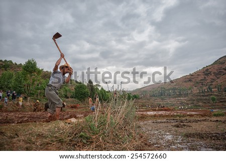 DALI, CHINA - JUNE 7: Chinese farmer works on farmland on June 7, 2014 in Dali, China. Chinese farmers have to work hard and only earn around $800 annual.