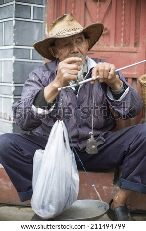DALI, CHINA - MAY 15: An old man is selling tea in the flea market on the street in Dali, China on May 15 2014. He is from a minority ethnic, called Bai.