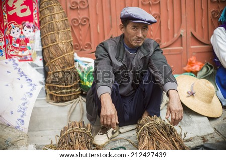 DALI, CHINA - MAY 15: An old man is selling tea in the flea market on the street in Dali, China on May 15 2014. He is from an ethnic minority called Bai.