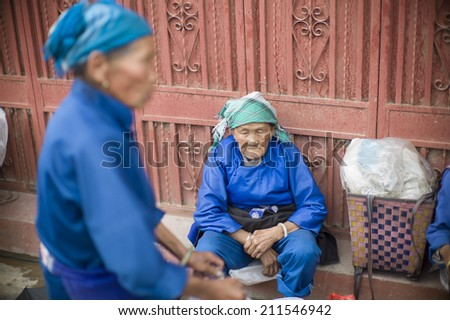 DALI, CHINA - MAY 15: An old woman is selling tea in the flea market on the street in Dali, China on May 15 2014. Yunnan is famous for tea.