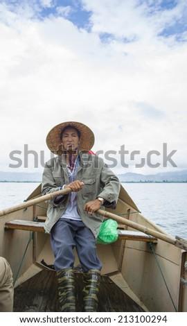 DALI, CHINA - MAY 16: man fishing on Erhai lake near Dali, Yunnan province, China on May 16 2014. Fishermen are Bai, a minority ethnic, and they use birds to fish.