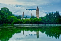 Dali's three ancient pagodas reflecting on a lake in a cloudy day