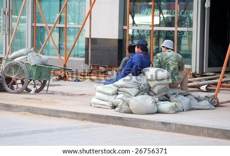 DALIAN, CHINA - MARCH 16: Three worders take a break from work at unidentified street in Dalian, China on March, 16, 2009. Dalian is one of the most heavily developed industrial areas in China.