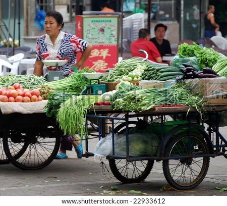 DALIAN, CHINA - SEPTEMBER 7: Woman trading vegetables in the street, September 7, 2008, Dalian, China. - stock photo