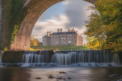 Dalkeith Country Park with waterfall and arch framing manor house on a sunny autumn afternoon makes for an ideal day trip from Edinburgh in Scotland.