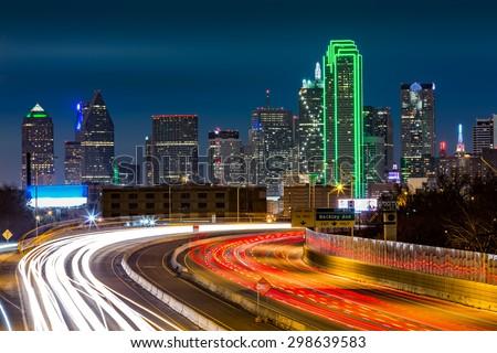 Dallas skyline by night The rush hour traffic leaves light trails on I-30 (Tom Landry) freeway. stock photo