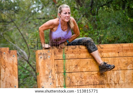 DALLAS, TEXAS - SEPTEMBER 15: Unidentified female participant climbs over a wooden wall obstacle in the Dash of the Titans Mud Run Race on September 15, 2012 in Dallas, Texas.